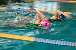 Two young students race during swim lessons