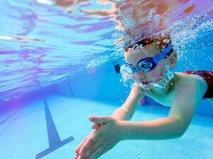 Little Boy diving underwater wearing swim goggles in a pool