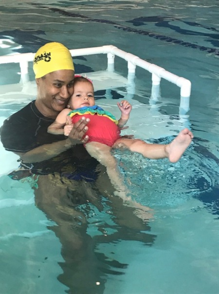 Brigette Tucker, Instructor, teaching young girl how to kick in the pool